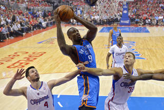 Oklahoma City Thunder forward Serge Ibaka, center, of Congo, puts up a shot as Los Angeles Clippers guard J.J. Redick, left, and forward Blake Griffin defend in the first half of Game 6 of the Western Conference semifinal NBA basketball playoff series, Thursday, May 15, 2014, in Los Angeles. (AP Photo/Mark J. Terrill)