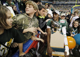 Baylor's Robert Griffin III, right, celebrates with fans after the Alamo Bowl college football game against Washington, Thursday, Dec. 29, 2011, at the Alamodome in San Antonio. Baylor pulled out a thrilling Alamo Bowl victory in the highest-scoring bowl game in history, beating Washington 67-56 in a record-smashing shootout Thursday night. (AP Photo/Darren Abate) ORG XMIT: TXDA122