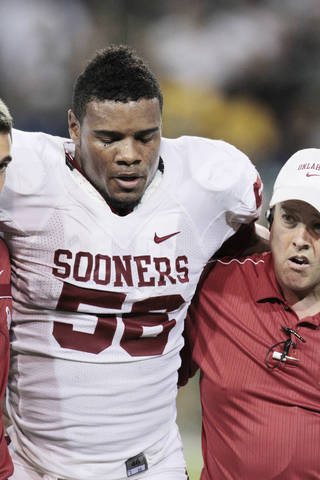 Oklahoma's Ronnell Lewis (56) is helped off the field after an injury during the college football game between the University of Oklahoma Sooners (OU) and the Baylor Bears (BU) at Floyd Casey Stadium on Saturday, Nov. 19, 2011, in Waco, Texas. Photo by Steve Sisney, The Oklahoman ORG XMIT: KOD