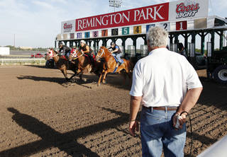 Ed Crane, starter for Remington Park, pushes the starter button to open the gates while holding it behind his back during a training session at Remington Park in Oklahoma City Wednesday, Aug. 28, 2013. Remington opened 25 years ago and Ed has worked there all 25 years. Photo by Paul B. Southerland, The Oklahoman PAUL B. SOUTHERLAND - PAUL B. SOUTHERLAND