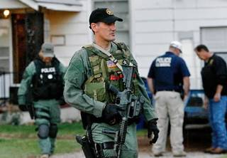 Officers are seen outside a Mustang home after making entry at dawn as part of a multi-agency drug raid that targeted meth operations throughout the state today. Photo by Jim Beckel