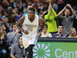 Fans applaud for Denver Nuggets guard Nate Robinson, front, after he hit a basket against the New Orleans Pelicans in the fourth quarter of the Nuggets' 102-93 victory in an NBA basketball game in Denver on Sunday, Dec. 15, 2013. (AP Photo/David Zalubowski)