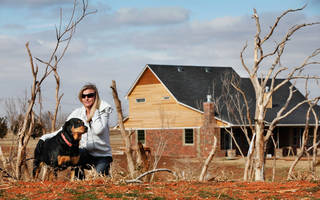 Tiffany Johnson and her pet rottweiler, Dutchess, are a few hundred yards south of the home she and her husband, Duane, are rebuilding near Waterloo and Sara roads. Their previous home was destroyed in an EF-5 tornado in May. Photo by Jim Beckel, The Oklahoman