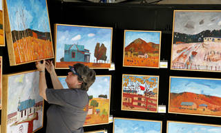 Laurie Dale Keffer tags paintings done by her husband, Oklahoma City artist Jim Keffer, in preparation for the 2012 Festival of the Arts. Photo by Doug Hoke, The Oklahoman DOUG HOKE