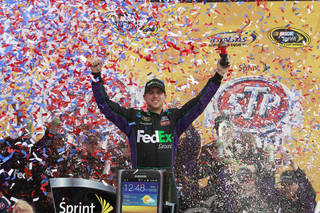 Denny Hamlin celebrates in Victory Lane after winning the NASCAR Sprint Cup Series auto race at Kansas Speedway in Kansas City, Kan., Sunday, April 22, 2012. (AP Photo/LAT, Michael L. Levitt) MANDATORY CREDIT ORG XMIT: KSML101