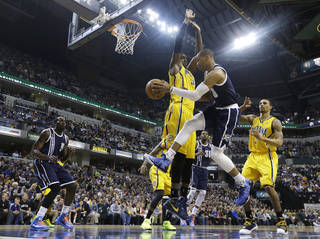 Oklahoma City Thunder's Russell Westbrook (0) passes to Kendrick Perkins (5) while defended by Indiana Pacers' Roy Hibbert (55) during the first half of an NBA basketball game on Friday, April 5, 2013, in Indianapolis. (AP Photo/Darron Cummings) ORG XMIT: NAF105
