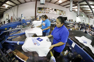 USA Screen Printing employees Eva Puentes, left, and Cinthia Patricio print T-shirts for Wednesday night's Oklahoma City Thunder playoff game in Oklahoma City. Steve Gooch - The Oklahoman