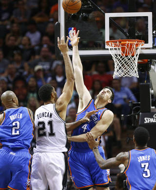 San Antonio's Tim Duncan (21) puts up a shot between Oklahoma City's Caron Butler (2), Nick Collison (4), and Perry Jones (3) during Game 2 of the Western Conference Finals in the NBA playoffs between the Oklahoma City Thunder and the San Antonio Spurs at the AT&T Center in San Antonio, Wednesday, May 21, 2014. Photo by Sarah Phipps, The Oklahoman