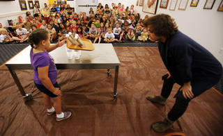 Grace Wilson, 6, attempts to knock away a tray with eggs sitting on it without harming the eggs while instructor Tyler Troy watches on during a June 13 Physics Funhouse event put on by the Metropolitan Library System and the Science Museum of Oklahoma at the Choctaw Library. Photo by KT King, The Oklahoman KT King - The Oklahoman