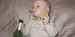 Toddler watching TV, holding beer bottle