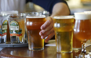 A server grabs a beer while loading a tray at Hale's Ales brewery and pub in the Ballard neighborhood of Seattle. AP File Photo Elaine Thompson - AP