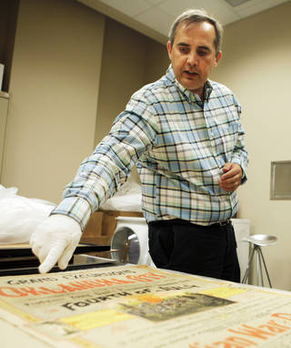 Oklahoma Historical Society Director of Research Chad Williams points to intricate details on the poster of the 1889 4th of July celebration in Oklahoma City. The poster was preserved in a time capsule buried in 1913 that was unearthed earlier this year. July 1, 2013 Photo by KT KING, The Oklahoman
