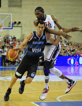 Pablo Prigioni, left, of Argentine senior national team drives past Carmelo Anthony of the U.S. during their pre-Olympic friendly basketball match at the Palau Sant Jordi in Barcelona, Spain, Sunday, July 22, 2012. (AP Photo/Manu Fernandez) ORG XMIT: MF116