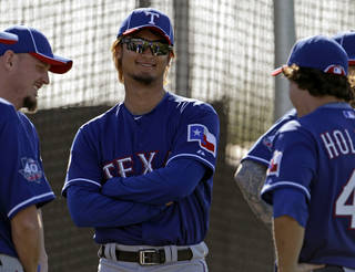 In this file photo taken Feb. 23, 2012, Texas Rangers pitcher Yu Darvish, center, from Japan, talks to teammates during spring training baseball in Surprise, Ariz. Darvish's next two starts will be televised. AP PHOTO