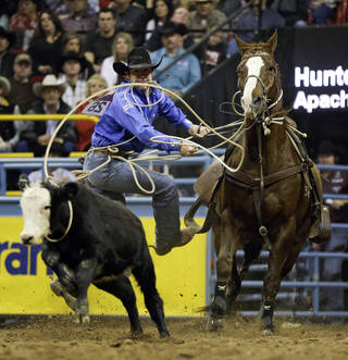 Hunter Herrin, of Apache, Okla., leaps of his horse while competing in the tie-down roping competition of the National Finals Rodeo, Wednesday, Dec. 12, 2012, in Las Vegas. (AP Photo/Julie Jacobson) ORG XMIT: NVJJ115