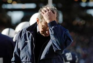 In this Nov. 6, 2004, file photo, Penn State coach Joe Paterno pauses on the sidelines during the fourth quarter of his team's 14-7 loss to Northwestern in State College, Pa. The NCAA has slammed Penn State with an unprecedented series of penalties, including a $60 million fine and the loss of all coach Joe Paterno's victories from 1998-2011, in the wake of the Jerry Sandusky child sex abuse scandal. (AP Photo/Carolyn Kaster,file)