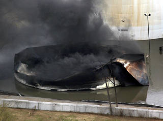CONOCOPHILLIPS TANK FARM: Glenpool: Tuesday, April 8, 2003 Fire in this oil storage tank caused evacuation of homes, schools and businesses in Glenpool Tuesday. Staff Photo by Steve Sisney