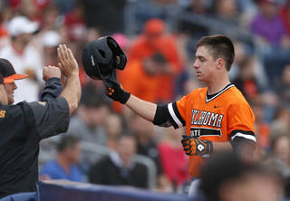 Oklahoma State's Donnie Walton is greeted at the dugout after scoring against Oklahoma during an NCAA college baseball game Friday, May 16, 2014, in Tulsa, Okla. (AP Photo/Tulsa World, Matt Barnard)