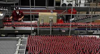 A worker keeps watch over a row of bottles at the Great Plains Coca-Cola Bottling Co. plant in Oklahoma City. BRYAN TERRY - THE OKLAHOMAN