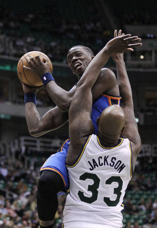 Oklahoma City Thunder guard Reggie Jackson, top, drives to the basket as Utah Jazz forward Darnell Jackson (33) defends in the second quarter during an preseason NBA basketball game on Friday, Oct. 12, 2012, in Salt Lake City. (AP Photo/Rick Bowmer) ORG XMIT: UTRB110