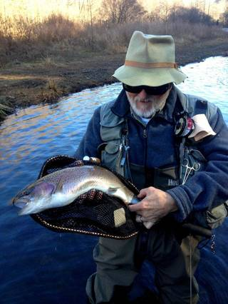 Clif Sikes of Earlsboro holds a fat 21-inch rainbow trout caught in the Evening Hole area of the Lower Mountain Fork River. Photo by Donny Carter