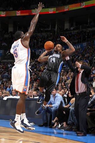 Orlando Magic's Jameer Nelson (14) tries to pass the ball as Oklahoma City Thunder's Kendrick Perkins (5) defends during the opening day NBA basketball game between the Oklahoma CIty Thunder and the Orlando Magic at Chesapeake Energy Arena in Oklahoma City, Sunday, Dec. 25, 2011. Photo by Sarah Phipps, The Oklahoman