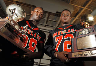 Douglass High School football players Jas'Sen Stoner, left, and Cayman Bundage pose for a photo with the Trojans' 2010 championship trophy and 2009 runner-up trophy at Douglass High School in Oklahoma City, Thursday, Aug. 18, 2011. Photo by Nate Billings, The Oklahoman ORG XMIT: KOD
