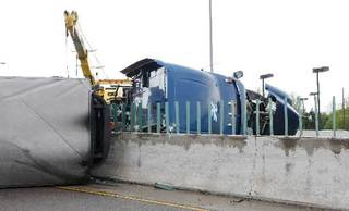 A semi cab and trailer on the center wall where it overturned on I-40 just west of Air Depot in Midwest City Thursday, May 9, 2013. The wreck shut down both east and west bound I-40. Photo by Paul B. Southerland, The Oklahoman