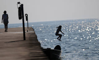A young swimmer jumps into Lake Michigan off of the pier in Montegue, Mich. AP Photo Elizabeth Conley - AP