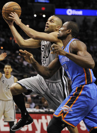 San Antonio's Tony Parker, left, shoots against Oklahoma City's Serge Ibaka during the first half of their game on Saturday in San Antonio. The Thunder beat the Spurs 113-100. Go to NewsOK.com for game results. AP photo