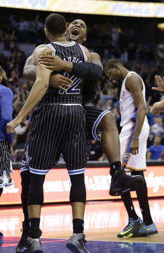 After making the game-winning shot, Orlando Magic's Tobias Harris, left, gets a hug from teammate Glen Davis as Oklahoma City Thunder's Kevin Durant, right, walks off the court after an NBA basketball game in Orlando, Fla., Friday, Feb. 7, 2014. Orlando won 103-102. (AP Photo/John Raoux)