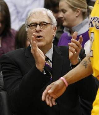 Los Angeles Lakers head coach Phil Jackson applauds guard Derek Fisher during the first quarter of an NBA basketball game against the Minnesota Timberwolves in Minneapolis, Friday, April 9, 2010. The Lakers beat the Timberwolves 97-88. (AP Photo/Ann Heisenfelt)