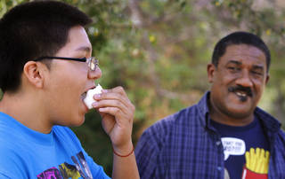 Brayan Parra eats a king-sized marshmallow. In background is Hiawatha Bouldin, group leader. Participants were divided into two teams; they competed against one another to determine which team would be the first to fully consume their allotted marshmallows. Local teens from around the metro have volunteered to be compliance checkers on local cigarette and alcohol vendors to make sure they aren't selling to underage teens. The group was honored at Eagle Ridge Institute on Aug. 25. Photo by Jim Beckel, The Oklahoman. Jim Beckel - THE OKLAHOMAN