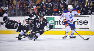 Edmonton Oilers center Teemu Hartikainen, right, controls the puck as Los Angeles Kings' Dustin Penner, left, Trevor Lewis (22) and Matt Greene defend during the first period of an NHL hockey game, Monday, April 2, 2012, in Los Angeles. (AP Photo/Richard Hartog) ORG XMIT: CARH104