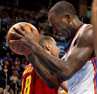 Sweat flies from the brow of Oklahoma City's Kendrick Perkins (5) as he hits himself with the basketball during the NBA basketball game between the Oklahoma City Thunder and the Cleveland Cavaliers at Chesapeake Energy Arena in Oklahoma City, Friday, March 9, 2012. Photo by Bryan Terry, The Oklahoman
