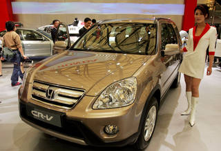A model poses in April 2005 by a Honda's CR-V at Auto Shanghai 2005 exhibition in Shanghai, China. AP File Photo EugeneHoshiko - AP