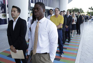 In this Oct. 23, 2013, file photo, Luis Mendez, 23, left, a student at Miami Dade College, and Maurice Mike, 23, a student at Florida International University, wait in line at a job fair held by the Miami Marlins at Marlins Park in Miami, Fla. The job market for new college graduates is brightening but remains weaker than before the Great Recession began. AP Photo Lynne Sladky -