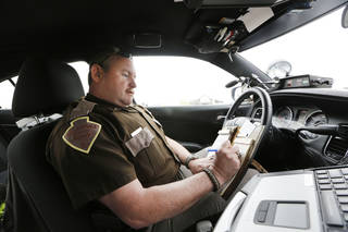Lt. Mark Reynolds, with the Oklahoma Highway Patrol, writes a warning for a motorist who was following to closely on west Interstate 40 in Oklahoma City on April 16, 2013. Photo By Steve Gooch, The Oklahoman Steve Gooch