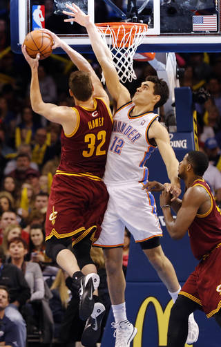 Oklahoma City's Steven Adams (12) defends on Cleveland's Spencer Hawes (32) during the NBA basketball game between the Oklahoma City Thunder and the Cleveland Cavaliers at the Chesapeake Energy Arena in Oklahoma City, Okla. on Wednesday, Feb. 26, 2014. Photo by Chris Landsberger, The Oklahoman