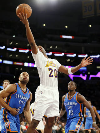 Los Angeles Lakers guard Jodie Meeks makes a reverse layup in front of Oklahoma City Thunder guard Derek Fisher, left, and guard Reggie Jackson during the second half of an NBA basketball game in Los Angeles, Sunday, March 9, 2014. The Lakers won 114-110, with Meeks scoring a career-high 42 points. (AP Photo/Danny Moloshok)