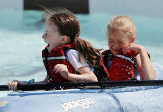Claire Foreman, 7, front, and Paige Hesse, 7, are splashed with water while kayaking during the Festival of the Child at Yukon City Park on Saturday. Photos by Nate Billings, The Oklahoman