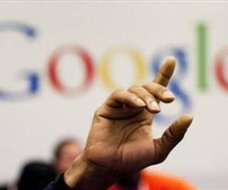 In this Oct. 17, 2012, file photo, a man raises his hand at Google offices in New York. (AP Photo/Mark Lennihan, File)