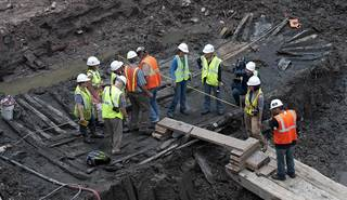 Workers and members of the media inspect the hull of a late 18th/early 19th century ship found at Ground Zer July 15, 2010 in New York. On the morning of July 13, workers excavating the site of the underground vehicle security center for the future World Trade Center hit a row of sturdy, upright wood timbers, regularly spaced, coming up through the mud. The 30 foot (9.1meter) long vessel remains were found 20-30 feet (6- 9.1 meter) below street level. AFP PHOTO/DON EMMERT (Photo credit should read DON EMMERT/AFP/Getty Images)