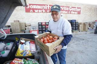 Volunteer Kevin Stone loads a trunk with donated food at the Community Service Center in Luther. PHOTO BY STEVE GOOCH, THE OKLAHOMAN Steve Gooch - The Oklahoman