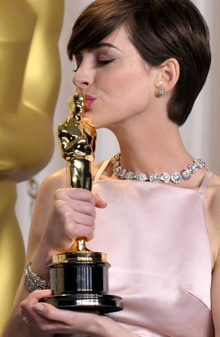 """Anne Hathaway in Prada poses with her award for best actress in a supporting role for """"Les Miserables"""" during the Oscars at the Dolby Theatre on Sunday Feb. 24, 2013, in Los Angeles. (Photo by John Shearer/Invision/AP) John Shearer"""