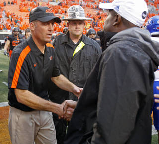 Oklahoma State head coach Mike Gundy and Kansas head coach Turner Gill shake hands following a college football game where the Oklahoma State University Cowboys (OSU) defeated the University of Kansas Jayhawks (KU) 70-28 at Boone Pickens Stadium in Stillwater, Okla., Saturday, Oct. 8, 2011 Photo by Steve Sisney, The Oklahoman