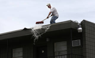Jimmy Reynolds brushes water off the roof of the Oakwood Apartments, 5824 NW 34, on Friday. PHOTO BY SARAH PHIPPS, THE OKLAHOMAN SARAH PHIPPS -