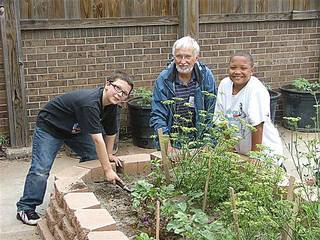 Student Alex Lynch, left, volunteer gardener Richard Carothers and student Isaiah Marshall harvest vegetables as part of a Del City Elementary School gardening project. Photo provided by Midwest City-Del City Public Schools