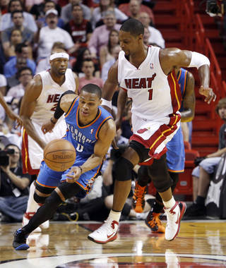 Oklahoma City Thunder's Russell Westbrook (0) recovers a loose ball as Miami Heat's Chris Bosh (1) defends in the first quarter of an NBA basketball game in Miami, Wednesday, March 16, 2011. The Thunder won 96-85. (AP Photo)