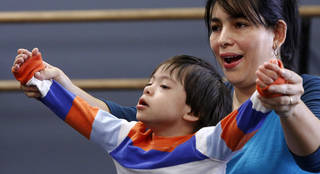 Dance instructor Katie Veenhuizen (not shown) works with Oscar Riano, Jr., 4, during a weekly ballet class for young children with Down syndrome held at the Oklahoma City Ballet, 7421 N. Classen Blvd. on Jan. 12, 2013. Helping Oscar is his mother, Magaly Riano, at right. Photo by Jim Beckel, The Oklahoman